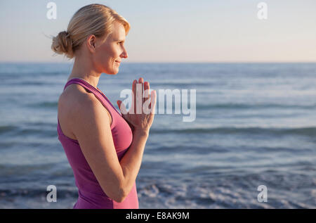 Woman in yoga prayer pose on the beach - Stock Photo