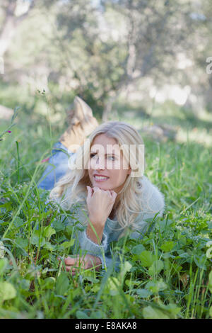 Woman lying on grass in garden - Stock Photo