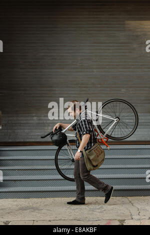 Male cycle messenger carrying cycle on sidewalk - Stock Photo
