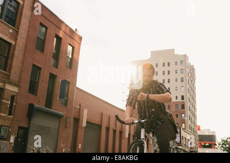 Male cycle messenger checking time on wristwatch - Stock Photo