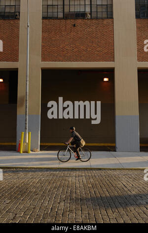 Male messenger cycling along city sidewalk - Stock Photo