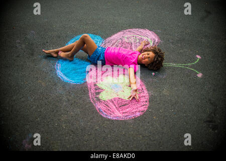 Young girl lying on floor between chalked butterfly wings - Stock Photo