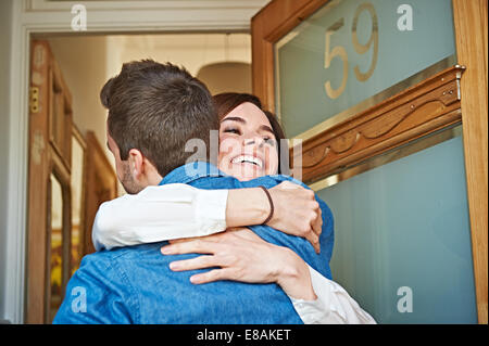 Couple hugging at front door - Stock Photo