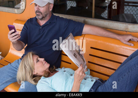 Mature couple sitting on bench on passenger ferry - Stock Photo