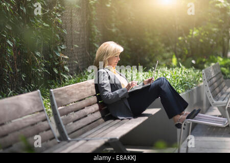 Mature businesswoman sitting on bench using laptop - Stock Photo