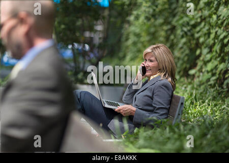 Mature businesswoman on phone with laptop - Stock Photo
