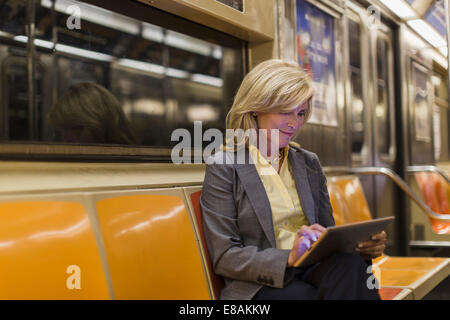 Mature woman sitting on subway train using digital tablet - Stock Photo