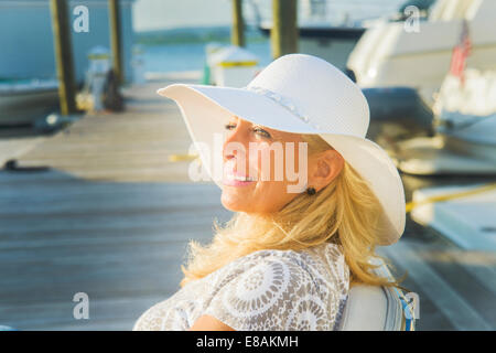 Mature woman sitting on harbor pier, Monmouth Beach, New Jersey, USA - Stock Photo