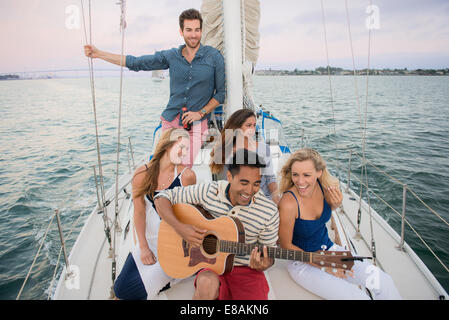 Friends on sailing boat, man playing guitar - Stock Photo