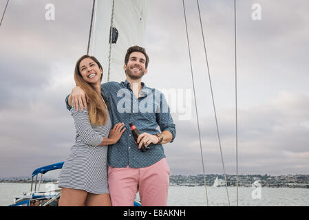 Mid adult couple on sailing boat, man with arm round woman - Stock Photo