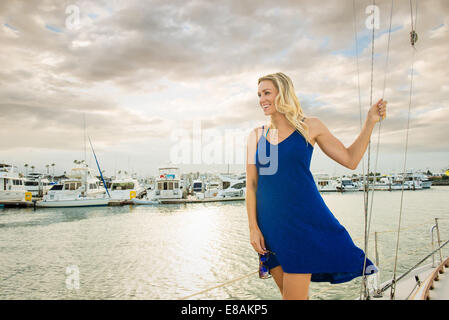 Young woman wearing blue dress on sailing boat, portrait - Stock Photo