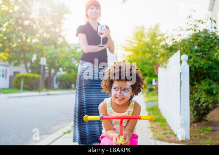Girl with painted face crouching on scooter on suburban street - Stock Photo
