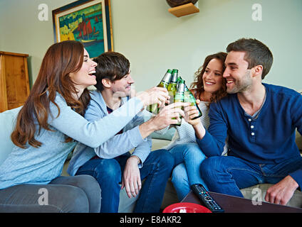 Group of friends watching sport in living room - Stock Photo