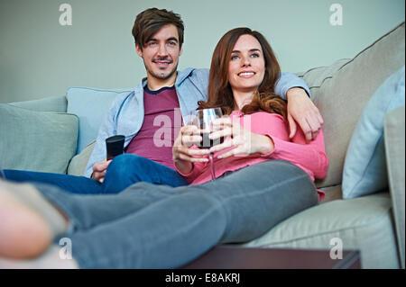 Couple enjoying wine on sofa - Stock Photo