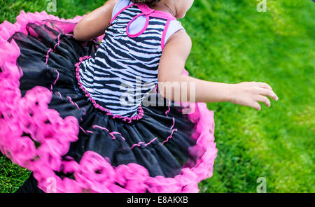 Cropped rear view of girl running in frilly party dress - Stock Photo