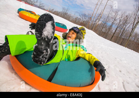 Boy laughing whilst tobogganing down snowy hill - Stock Photo