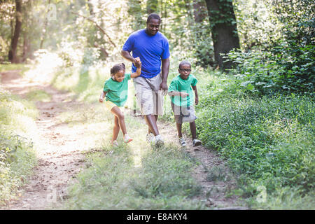 Father walking through forest with daughter and son at eco camp - Stock Photo