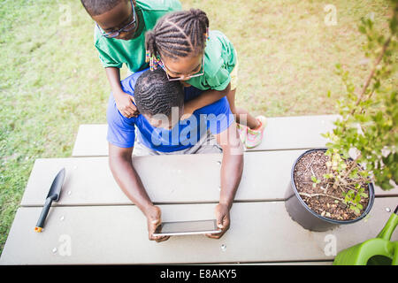 High angle view of father looking at digital tablet with daughter and son at eco camp - Stock Photo