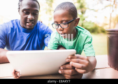 Father looking at digital tablet with son at eco camp - Stock Photo