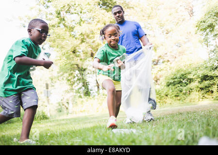 Father picking up litter with son and daughter at parkland eco camp - Stock Photo