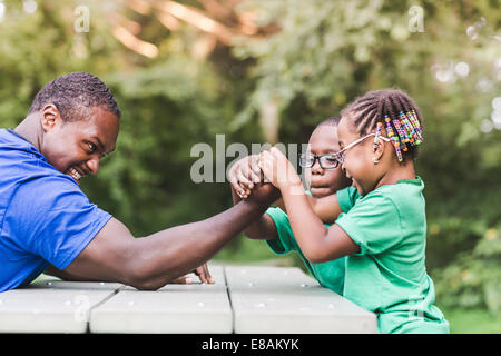 Father arm wrestling with daughter at parkland eco camp - Stock Photo