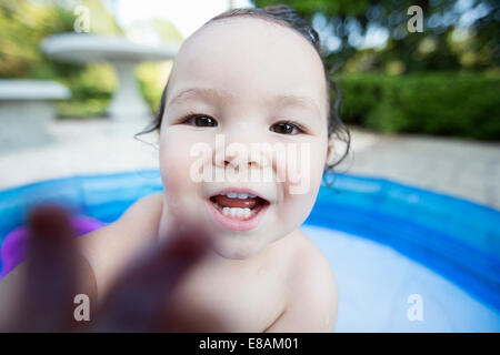 Close up candid portrait of a baby girl in paddling pool - Stock Photo