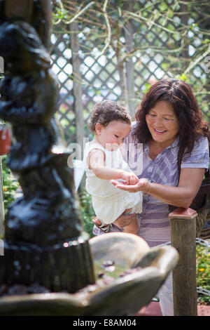 Grandmother and granddaughter feeding at fishpond in zoo - Stock Photo