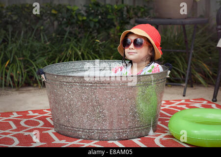 Portrait of girl wearing sunhat and sunglasses sitting in bubble bath in garden - Stock Photo