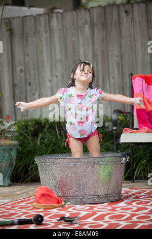 Girl standing in bathtub in garden with arms outstretched - Stock Photo