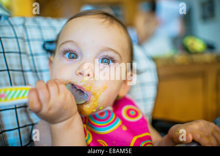 Portrait of baby girl eating from spoon - Stock Photo
