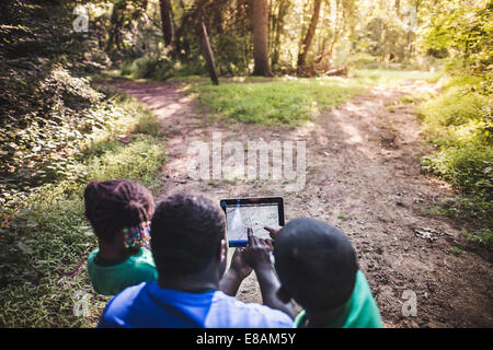 Father with daughter and son navigating with digital tablet in forest eco camp - Stock Photo