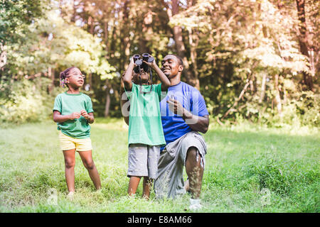 Father with son and daughter bird watching in eco forest camp - Stock Photo
