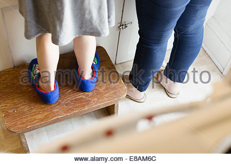 Legs of mid adult mother next to daughter standing on stool in kitchen - Stock Photo