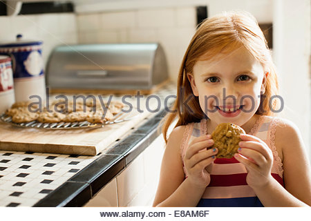 Portrait of girl eating biscuit in kitchen - Stock Photo