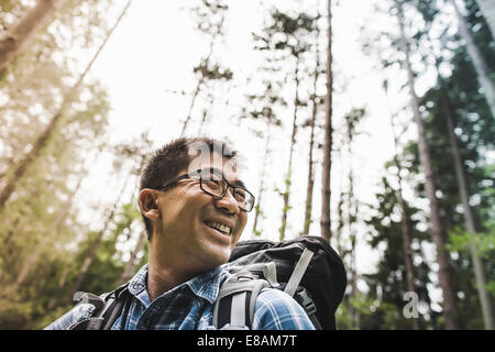 Hiker in forest wearing glasses, smiling - Stock Photo