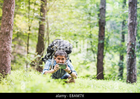 Hiker taking photo on camera phone in forest - Stock Photo