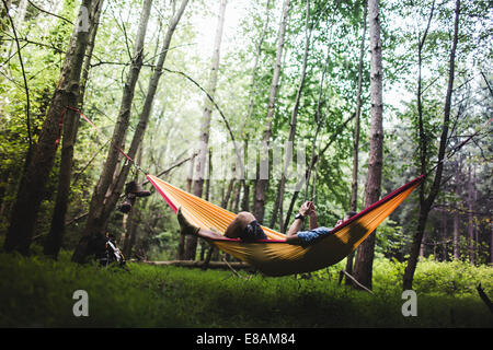 Hiker lying in hammock in forest using digital device - Stock Photo