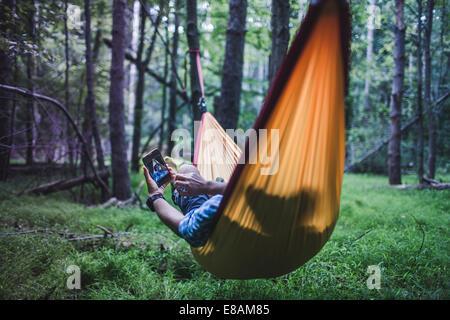 Hiker lying in hammock in forest using digital device - Stock Photo