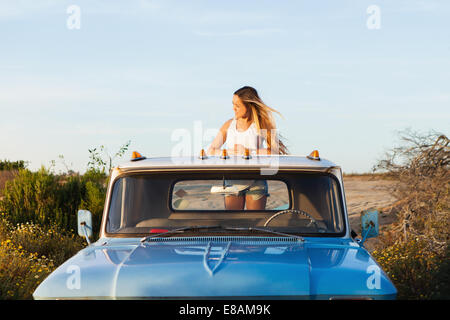 Young woman looking from the back pickup truck - Stock Photo