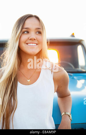 Portrait of young woman leaning against pickup truck - Stock Photo