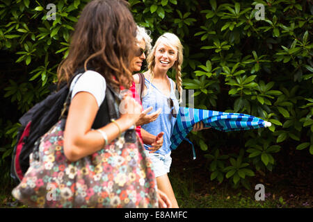 Mature mother and two daughters chatting and walking - Stock Photo