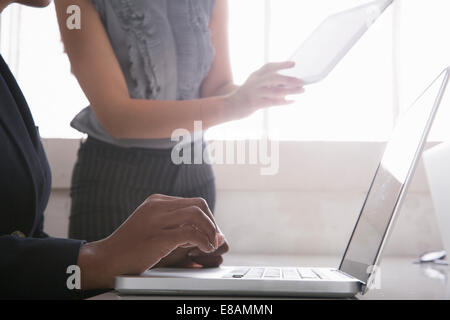 Woman using laptop, woman in background holding digital tablet - Stock Photo