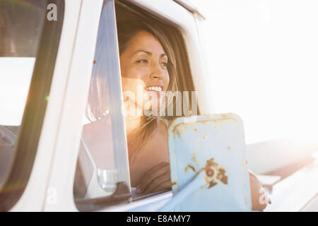 Young female surfer looking out of pick up truck window, Leucadia, California, USA - Stock Photo