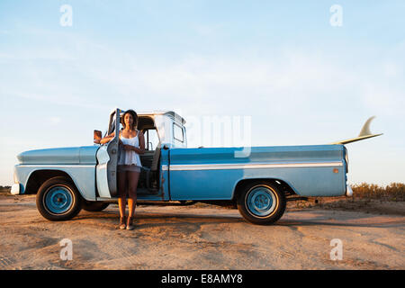 Portrait of young female surfer leaning on pick up truck door, Leucadia, California, USA - Stock Photo