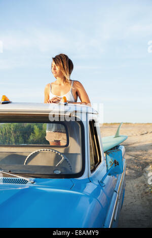 Young female surfer looking from back of pick up truck, Leucadia, California, USA - Stock Photo