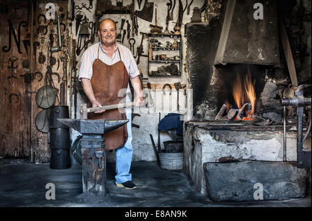 Portrait of senior male blacksmith in traditional workshop, Cagliari, Sardinia, Italy - Stock Photo