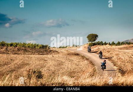 Rear view of four friends riding motorcycles on rural road, Cagliari, Sardinia, Italy - Stock Photo