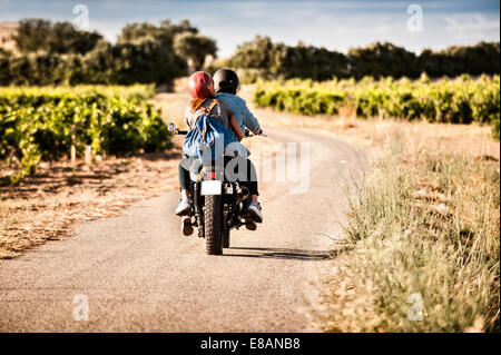 Rear view of mid adult couple riding motorcycle on winding rural road, Cagliari, Sardinia, Italy - Stock Photo