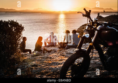 Five motorcycling friends taking a break on coast at sunset, Cagliari, Sardinia, Italy - Stock Photo
