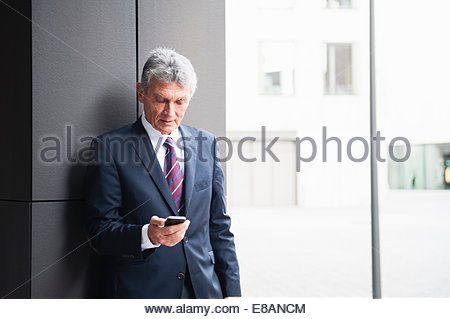 Senior businessman leaning against wall texting on smartphone - Stock Photo